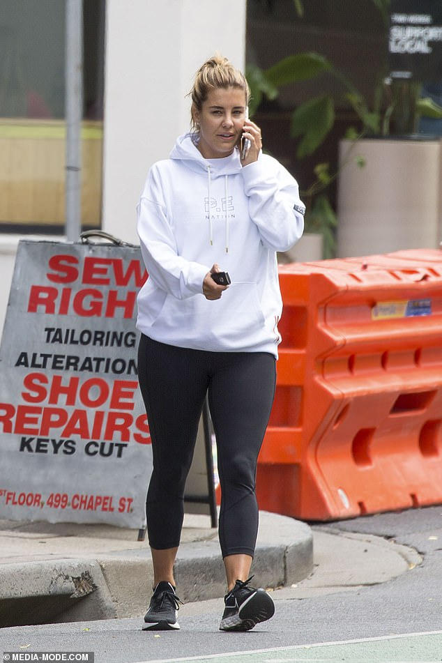 Sporty chic: She stepped out in a trendy athleisure ensemble as she was busy chatting on the phone.She teamed a white oversized hoodie from P.E Nation, Pip Edwards' label, with fitted black leggings, and a pair of black trainers