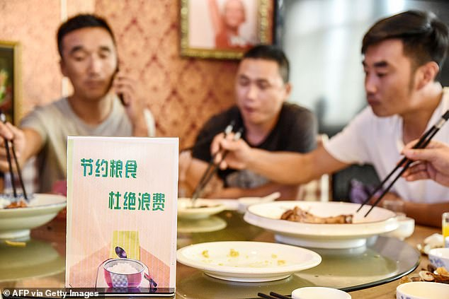 China has waged a war on food waste with a drafted law to ban it. Pictured, a sign encouraging people not to waste food is seen at a restaurant in Handan, northern China's Hebei province