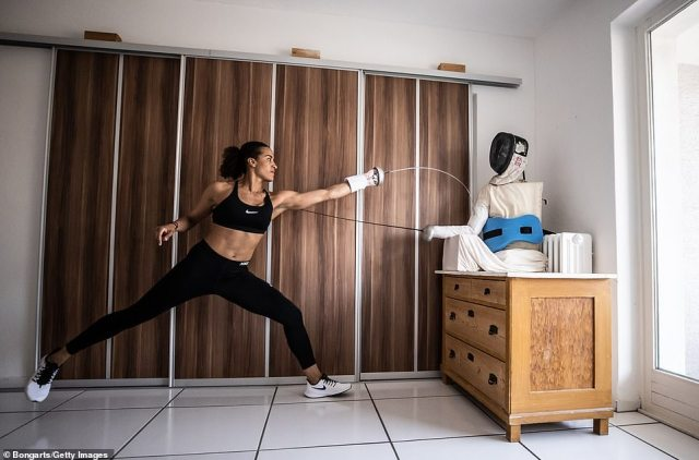 German epee fencer Alexandra Ndolo trains with a self made puppet in her apartment on April 09, 2020 in Cologne, Germany. Ndolo normally trains with a coach and team mates, but due to the lockdown she, like many professional athletes, is having to improvising training sessions to stay fit