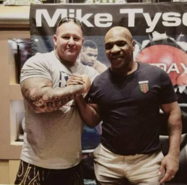 Martin is pictured shaking hands with US boxing legend Mike Tyson (right)