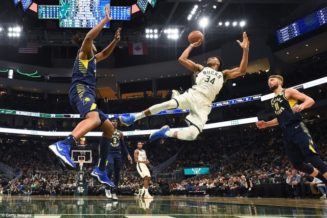 NBA MVP Giannis Antetokounmpo shoots a wild floater over Indiana Pacers center Myles Turner during a game in March