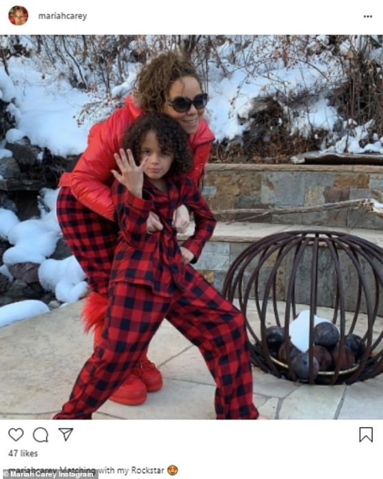 Beloved family: Mariah Carey (50) teamed up with her Moroccan son 'Rockstar' in red and black plaid pajamas as they posed in her snowy backyard