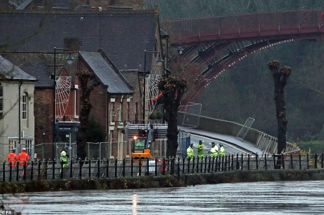 Environment Agency staff place flood barriers on a bank of the high River Severn near Ironbridge in Shropshire yesterday