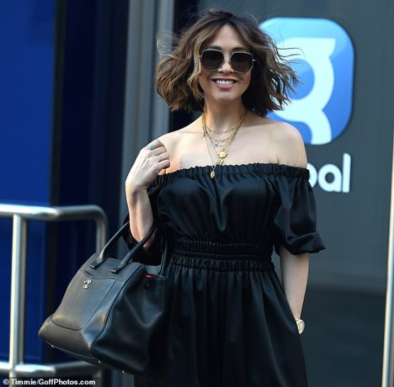 The wind blew: The brunette beauty wore short strands in waves as they blew in the wind as she approached the offices