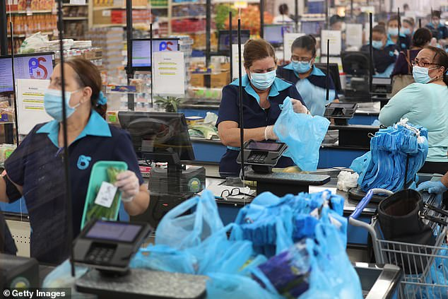 Diana Rivero stands behind a partial protective plastic screen and wears a mask and gloves as she works as a cashier at the Presidente Supermarket on April 13, 2020 in Miami, Florida. Grocery store workers will be amongst those prioritized next, after medical workers, the CDC said today