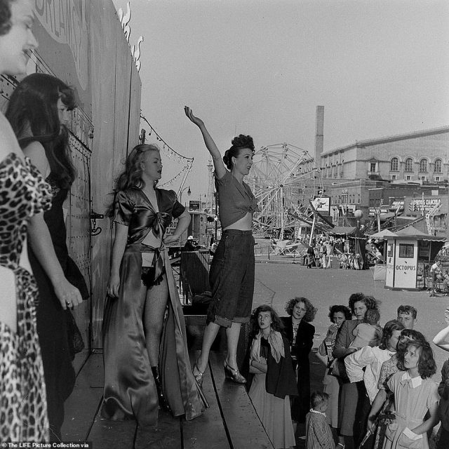 Burlesque star Gypsy Rose Lee introduces fellow performers to carnival-goers ahead of her racy prime-time evening show. She was paid $10,000 per week to join the carnival in 1949 - roughly $110,000 in today's dollars. Beginning in 1937, Lee attempted to retire from erotic dancing many times but was always drawn back to the stage. 'I always go where the dough is,' she remarked.  Lee earned her legendary status as a sophisticated and witty striptease artist. Unlike the herky-jerky flesh offerings of other dancers, she invented a new style that was 'more tease than strip' and left the audience wanting more