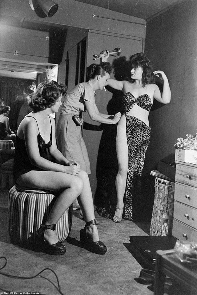 Backstage in Memphis, Gypsy (center) fastens a barely-there skirt to one of her dancers. The legendary burlesque dancer was involved in every aspect of her show from the creative concept to costume design. She shunned the use of zippers, buttons and eye-hooks in favor of sewing pins which made it easier for her to disrobe. Far be it from her to suffer an untimely zipper jam during a scintillating performance