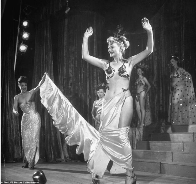 Burlesque dancer Gypsy Rose Lee (left) helps dancer Florence Bailey perform a reverse striptease act during Lee's carnival tour across the country. The finale of her show, according to the Tulsa World newspaper, was the story of Cinderella, with Lee as the Fairy Godmother, wearing a 97-pound dress containing over one million hand-sewn rhinestones