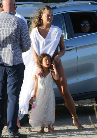 Chrissy Teigen keeps daughter Luna close as husband John Legend carries son Miles in St. Barts