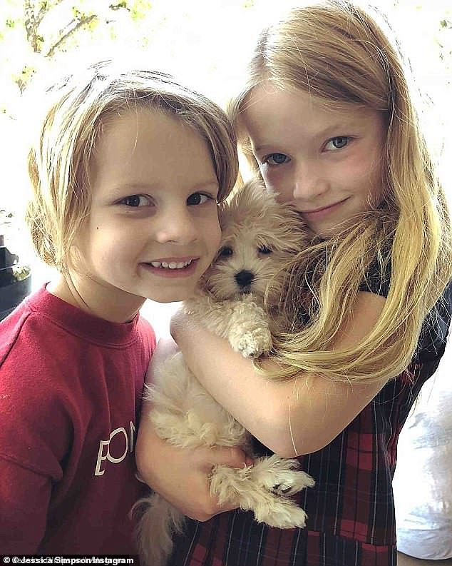 Family time: Dixie was adopted by Simpson and her husband Nick Johnson in 2018; the pooch is seen with two of the couple's children, Ace and Maxwell