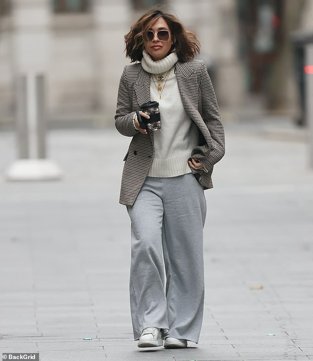 Keeping warm:She sported a white jumper with a large roll neck and a long checked blazer which she left open