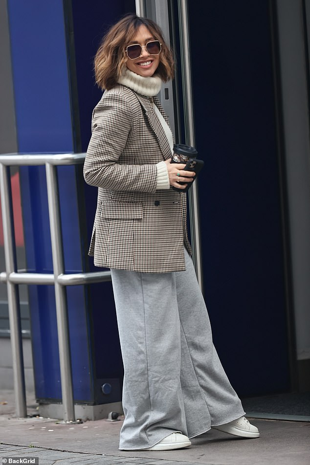 Wearing a smile: She carried a coffee cup and her phone as she finished off the look with a pair of flat white trainers