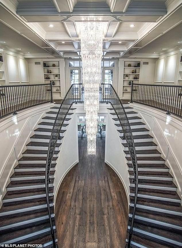 Wow: Inside the home is a stunning foyer with a double staircase and custom chandeliers, which 'give the appearance of a diamond waterfall,' the real estate site reported