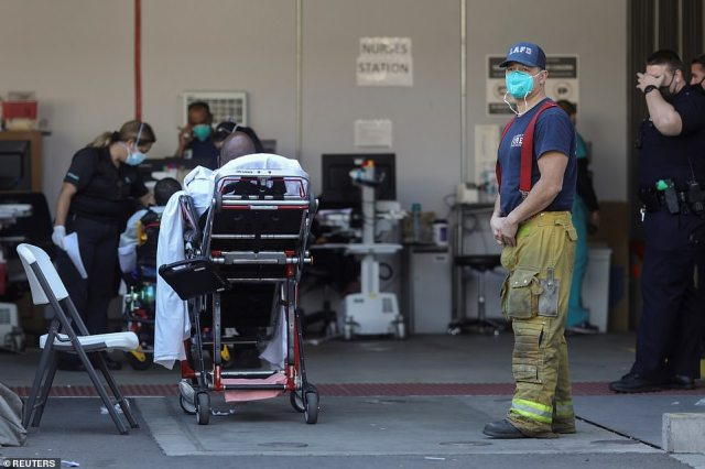 Ambulance crews wait to admit patients outside of the MLK Community Hospital emergency entrance during a surge of coronavirus disease cases in Los Angeles on Saturday