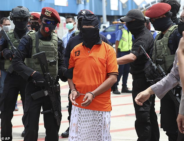 Zulkarnaen (pictured in police custody on December 16) was transferred to Jakarta for questioning alongside other JI suspects and revealed how the group raised funds