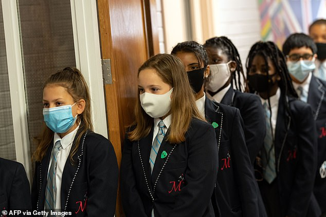 The Education Secretary is facing mounting pressure from experts to reconsider school closures (pictured: School children wear face masks, library image) in January, amid concern that the new strain is more easily spread among children