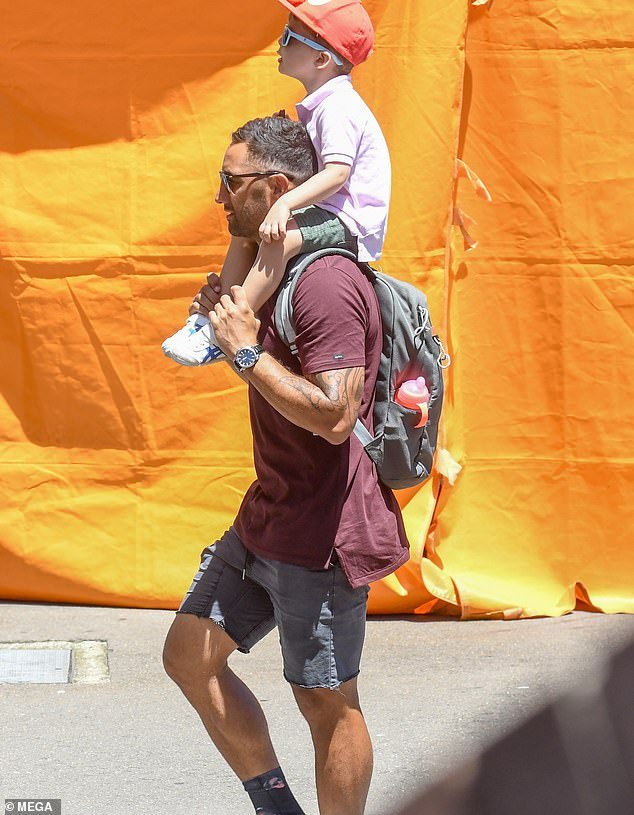Precious: Benji, 35, carried Benjamin on his shoulders. The toddler looked cute as a button in a pink polo shirt, khaki shirts and sneakers, as well as an adorable Elmo-themed red cap
