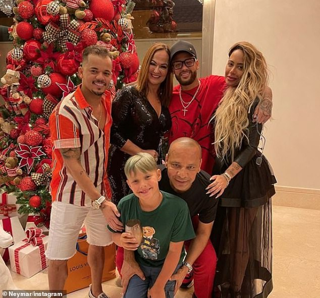 Neymar (top row, centre right) poses for a picture on Christmas day with sister Rafaella Santos (right), son Davi Luca (bottom, centre left), his mum Nadine Goncalves (top row, centre left), his father Neymar Sr (bottom row, centre right) and close friend Jota Amancio (left)
