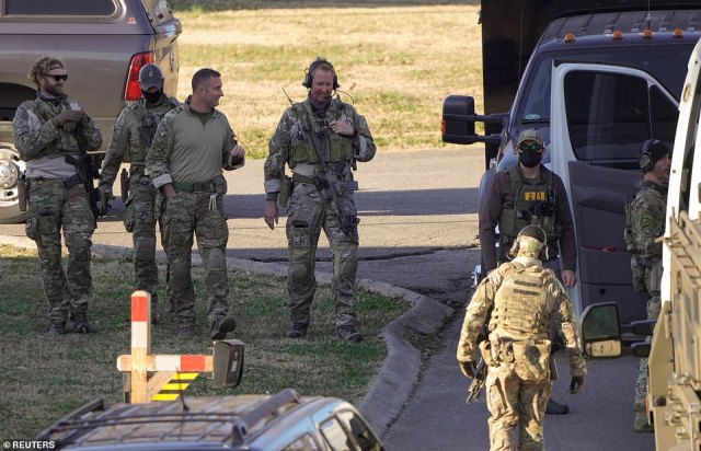 Law enforcement officers gather to investigate the house which was scanned for further bombs