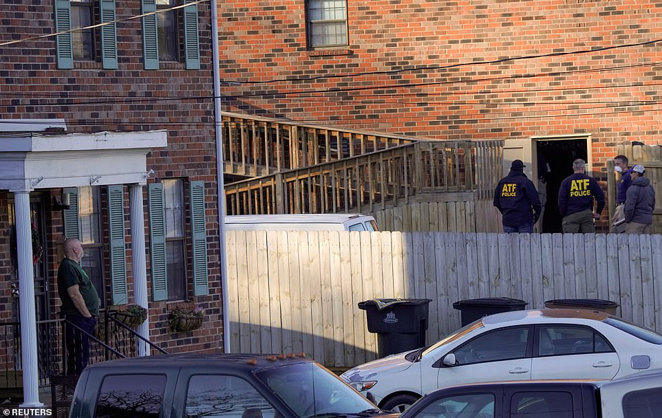 Neighbors watch on as investigators search the home allegedly linked to the bombing suspect