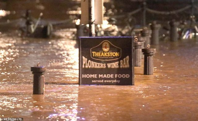 Drinkers headed out despite plunging temperatures and some flooding in York, with the Plonkers Wine Bar sign pictured here submerged
