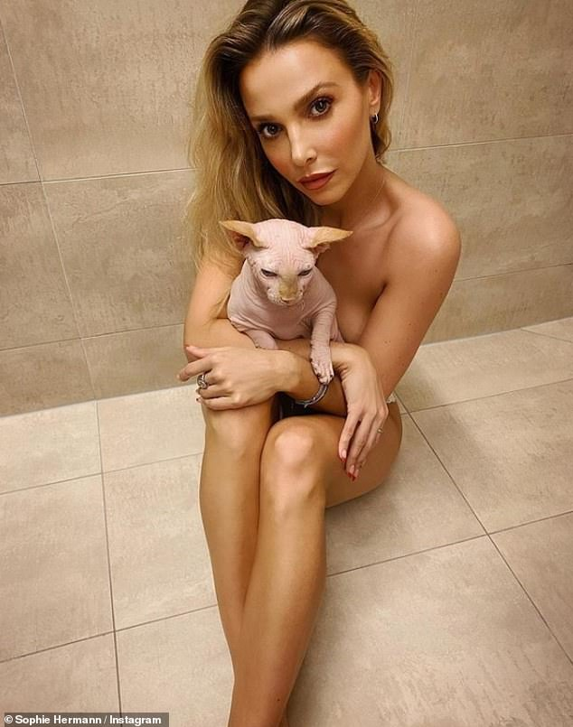 Silky smooth:Made In Chelsea star Sophie Hermann was reunited with her beloved pet cat over Christmas and honoured the hairless Sphinx cat but stripping down to nothing and cuddling up to him