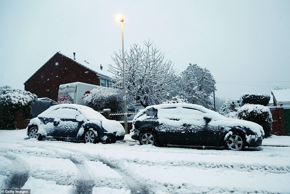 The warnings are set to last until 6pm on Monday. Pictured: Cars are covered in snow as heavy snow falls down on the West Midlands over night