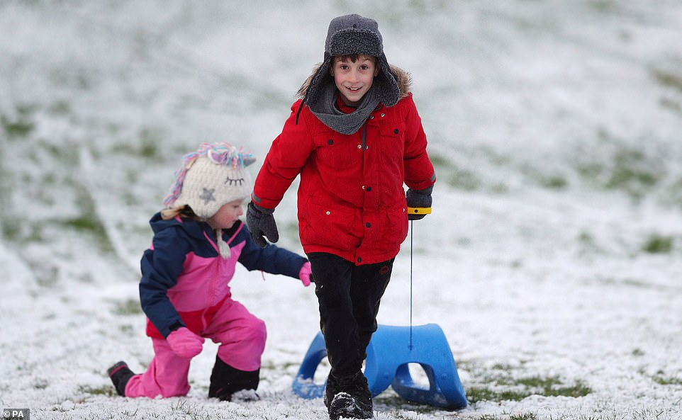 Daniel Brym, aged 8, and his sister Emma, aged 4, sledging on Camp Hill, Woolton, Liverpool, after snow fell overnight