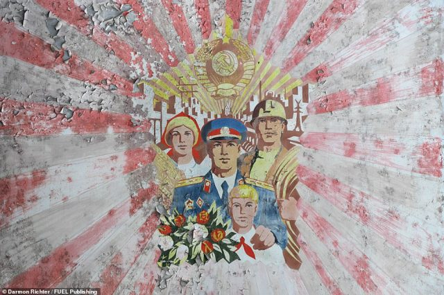 A mural on a residential building in Pripyat. This Socialist-realist mural depicts virtuous citizens - a farmer, a firefighter, a police officer, and a young pioneer - under a radiant Soviet crest