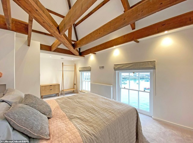 The bedroom on the first floor features a high vaulted ceiling and large windows and offers an amazing view of St Ives harbour