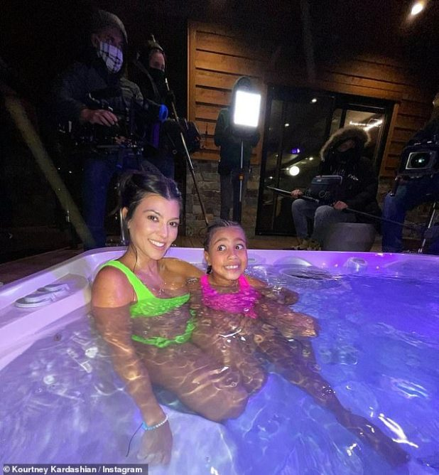 Shiny Girls: The 41-year-old reality superstar, sitting in a hot tub in a neon green bikini, smiled while niece North was in a hot pink one piece