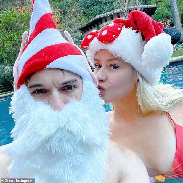 Mrs Claus: The 40-year-old wore a Mini Mouse Santa hat with her swimsuit as she wrote to the 25-year-old Rutler in the pool: 'Holiday Photo Dump - Stay Home Edition'