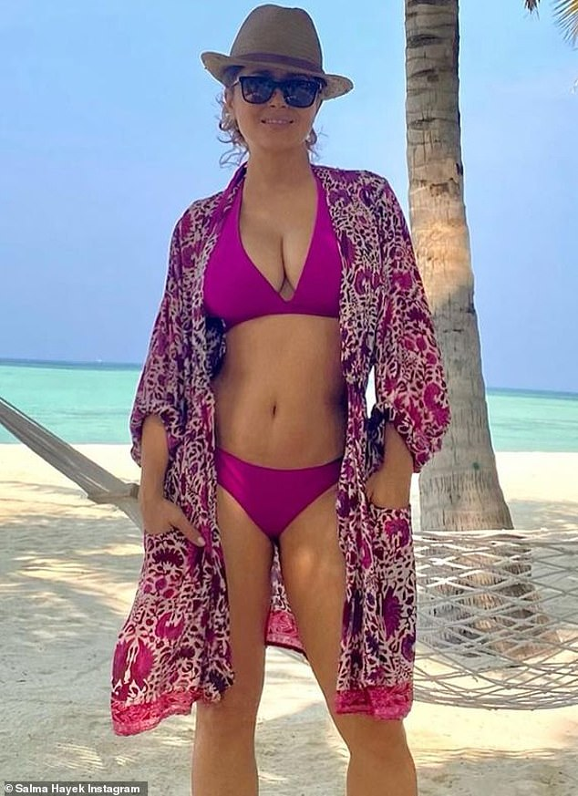 Grateful for being healthy: Posing up by the water, the agelessly beautiful 54-year-old showed off her ample cleavage and enviably taut midriff in a clinging purple two-piece