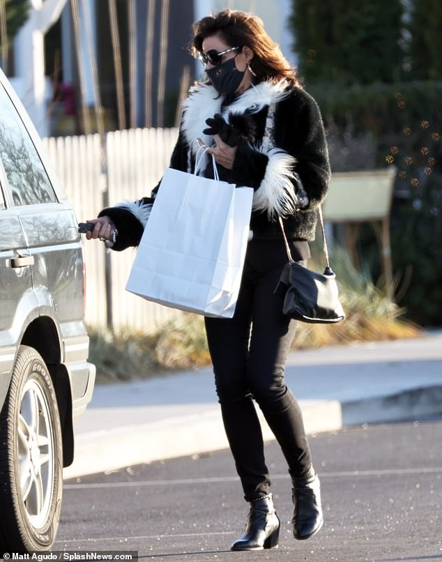 Staying cozy: The reality television star was seen wearing a warm black overcoat with white fur lining