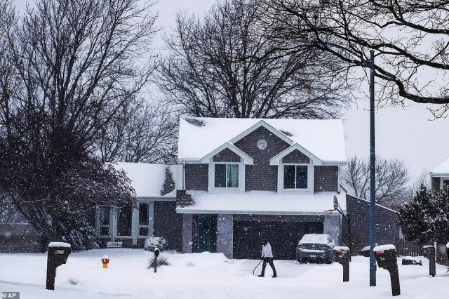 Brandon Franks shovels snow out of his driveway in the Pepperwood neighborhood of Omaha on Tuesday