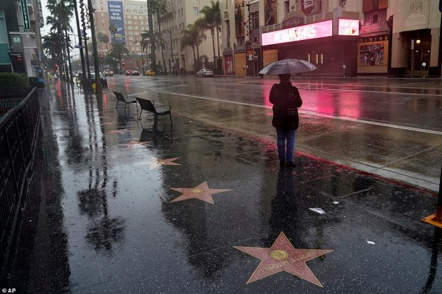 A woman waits at a bus stop in the rain Monday, Dec. 28, 2020, along Hollywood Boulevard in Los Angeles