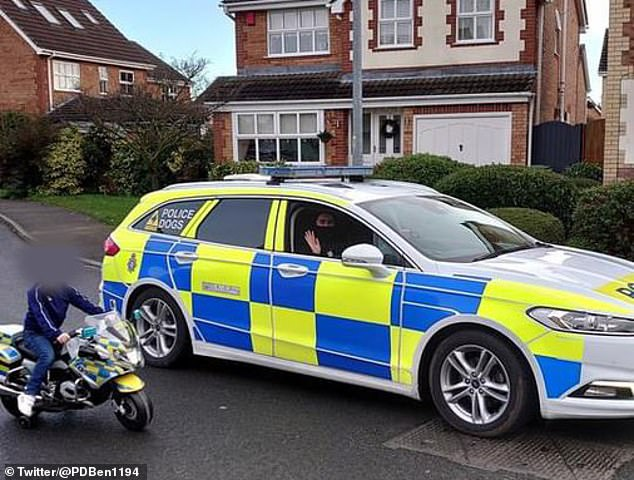 The Humberside police dog handler posed for a photo with the young racer, who sits on his toy police motorbike