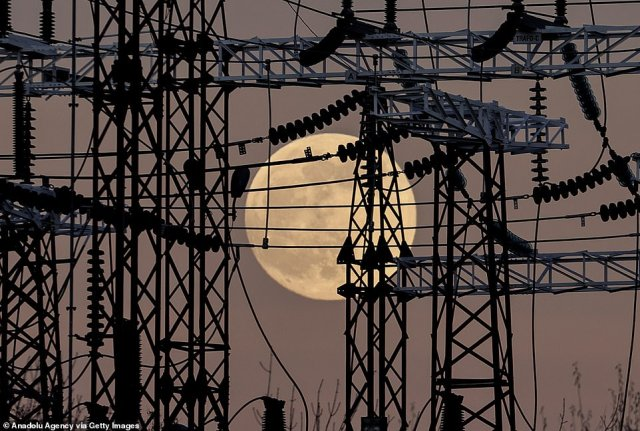 The full moon is seen rising behind electricity pylons in Ankara, Turkey on Tuesday
