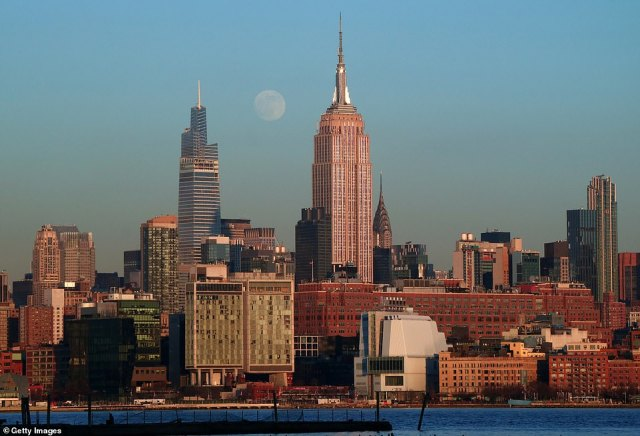 The moon rises between One Vanderbilt and the Empire State Building in New York City