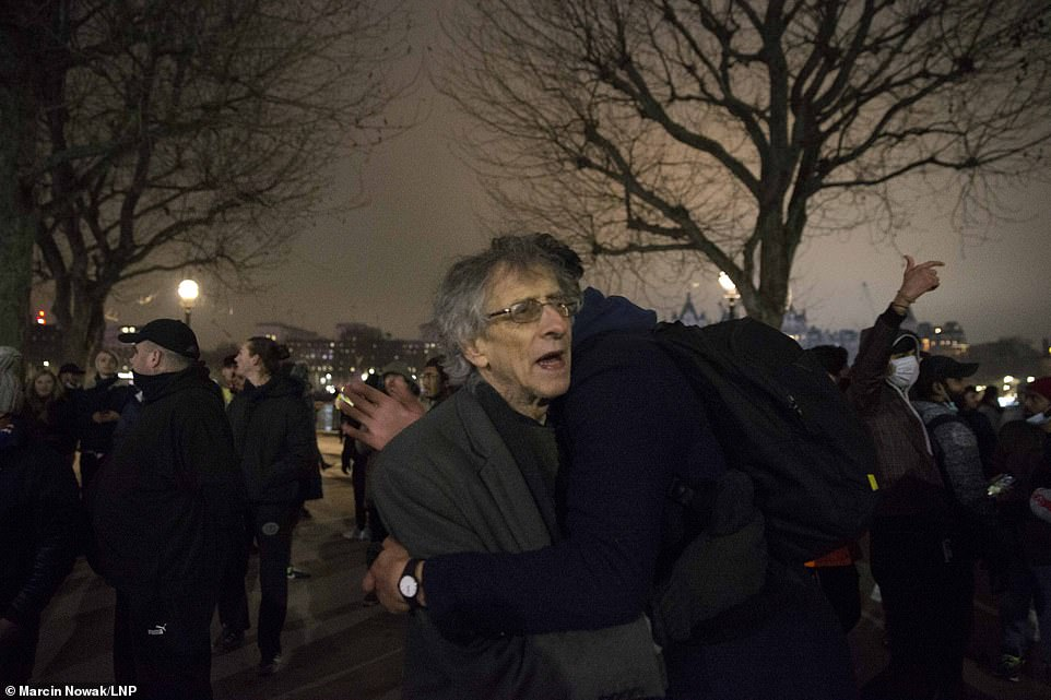 Piers Corbyn was hugged by a fellow lockdown protester on the banks of the River Thames last night, as other drank to celebrate the New Year