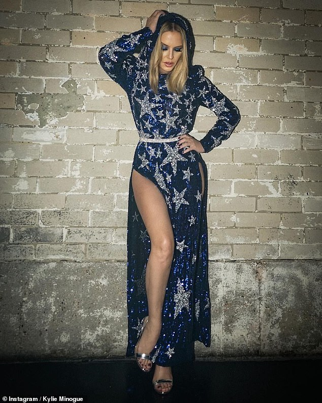 Kylie Minogue exudes glamour in a blue sequinned gown with a VERY racy thigh-high split