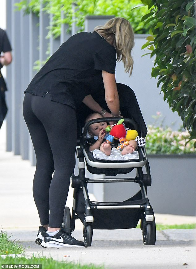 Doting:At one point, Sylvia could be seen attending to her son as they walked around, who had some toys in the pram to keep him entertained