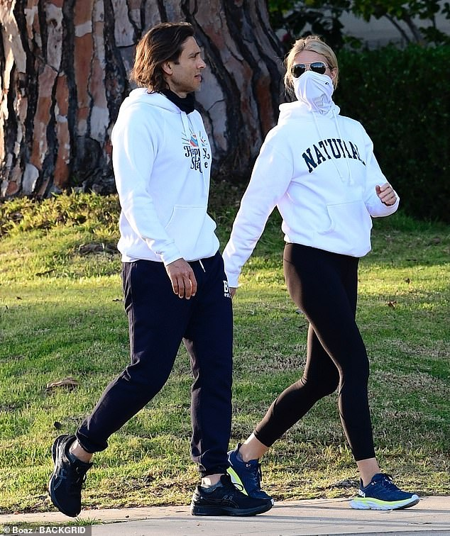Sporty: Gwyneth's hoodie was from Museum of Peace and Quiet and read 'Natural' across her chest, and she also had on black leggings and blue Hoka One One trainers