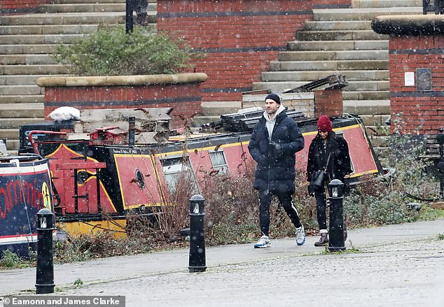 Stroll: Sair, 32, wore a long trench over a Burberry scarf, black jeans and chunky boots. She added mittens and a red beanie hat to the look