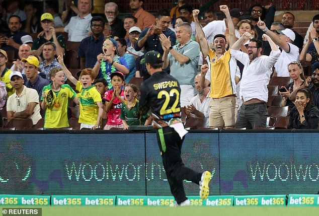 Fans celebrate as Australia' Mitchell Swepson catches out India's Shikhar Dhawan off the bowling of Adam Zampa at the Second Twenty20 International on December 6
