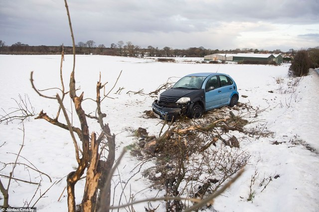 A car sits in a snowy field after leaving the road near Great Broughton on The North Yorkshire Moors this morning
