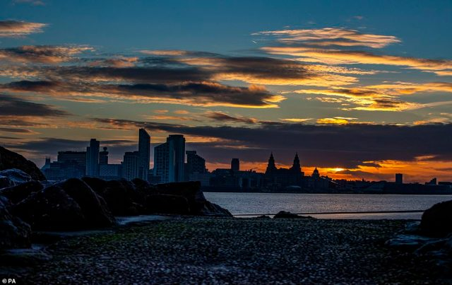 The view of the sun rising behind the Liverpool skyline from New Brighton beach, Wirral, this morning
