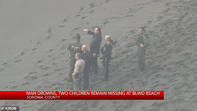 First responders are seen standing on the beach during Sunday's search operation
