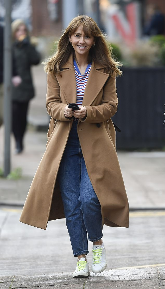 Glam: The soap star looked effortlessly chic in a longline camel coloured coat, which she teamed with indigo jeans and a striped T-shirt