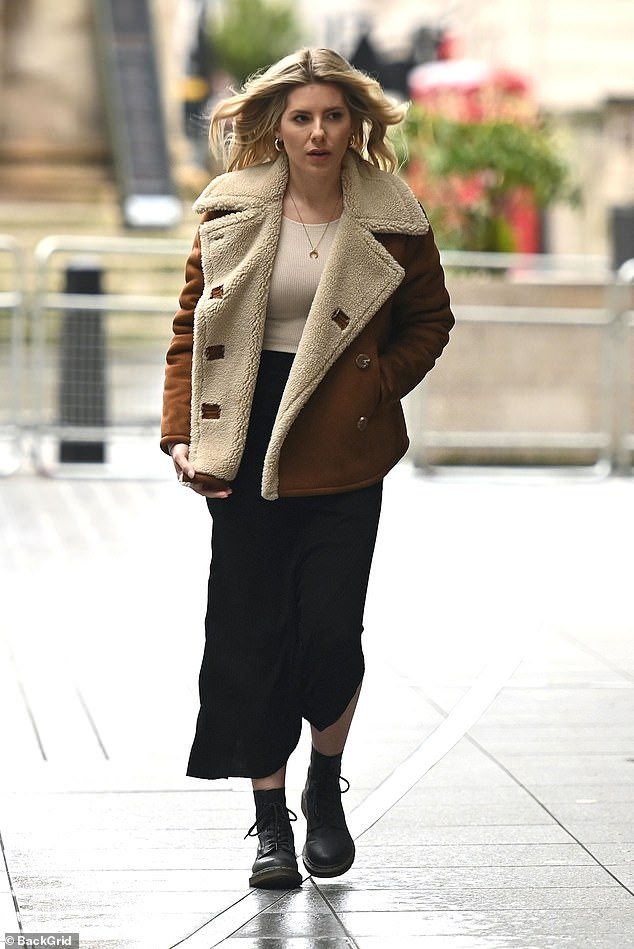 Coy: The Radio One presenter, 33, looked stylish in a tan suede and bourg coat and a black midi skirt but hid her ring finger in her pocket